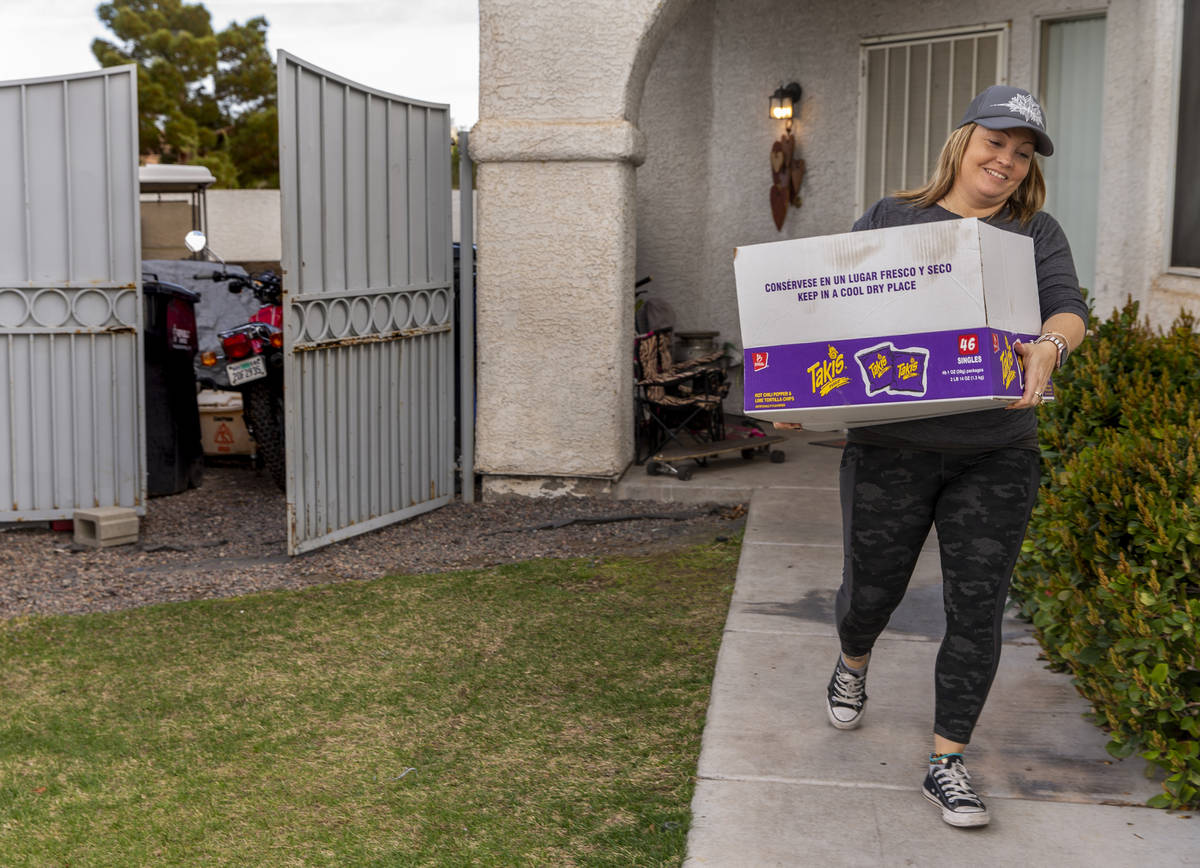 Kat Morris retrieves another donated box of food and supplies on her rounds with the COVID-19 B ...