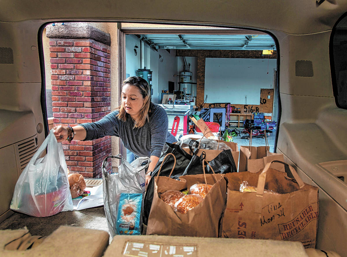 Kat Morris fills the back of her car with food and supplies for another donation drop with the ...