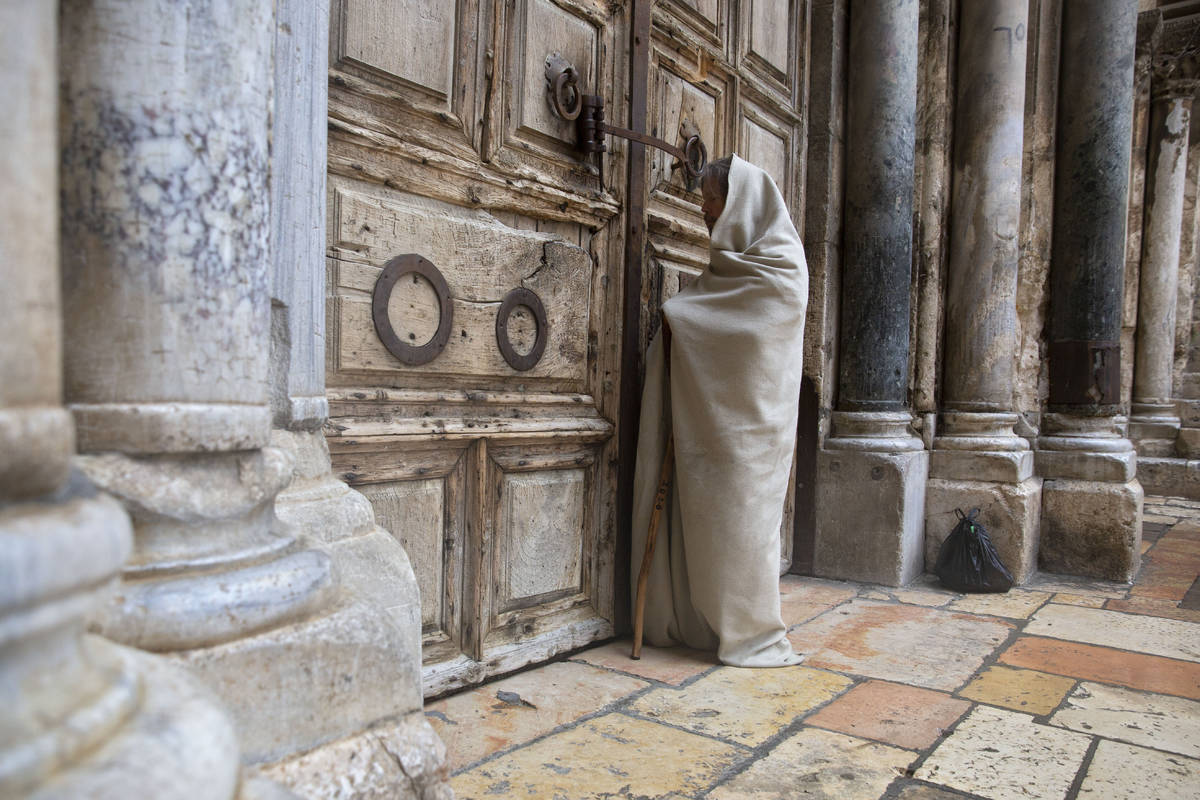 A Christian worshiper stands at the closed door of the Church of the Holy Sepulchre, believed b ...