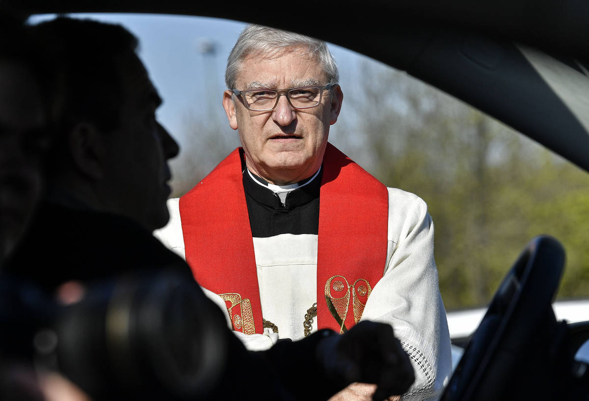 Priest Frank Heidkamp talks to believers in their cars prior a Good Friday church service at a ...