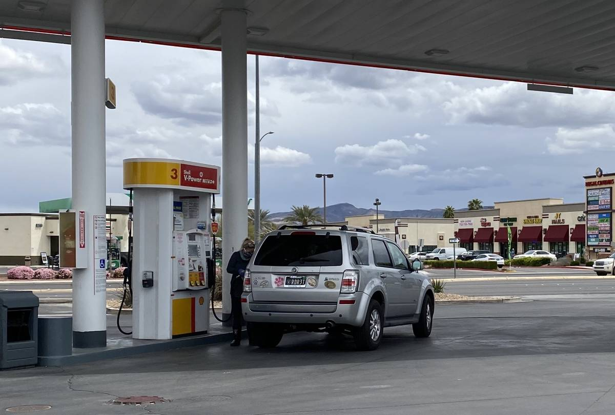 A woman in a Raiders face masks pumps gas at the Shell Station on south Eastern near the 215 Be ...