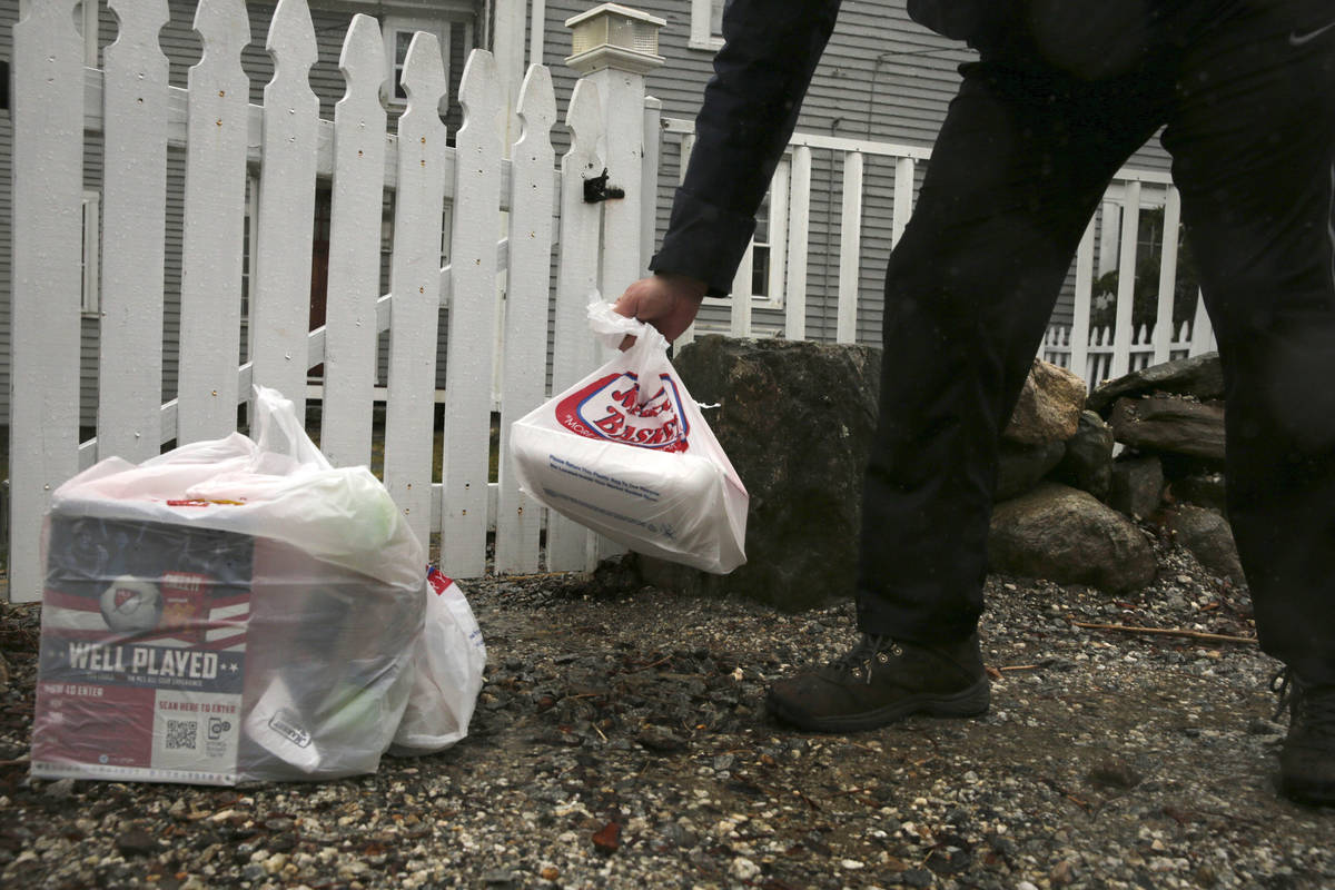 Instacart worker Arthur Berte leaves groceries at the gate of a home in East Derry, N.H., Frida ...