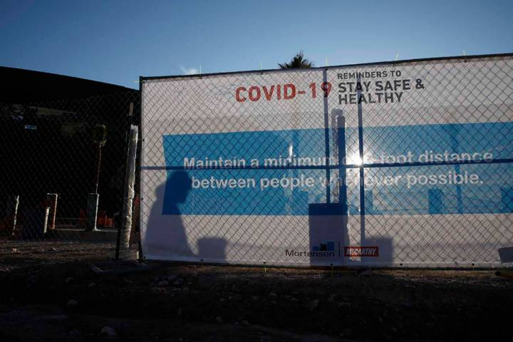 A worker casts a shadow on a sign with guidelines for protection from COVID-19 as construction ...