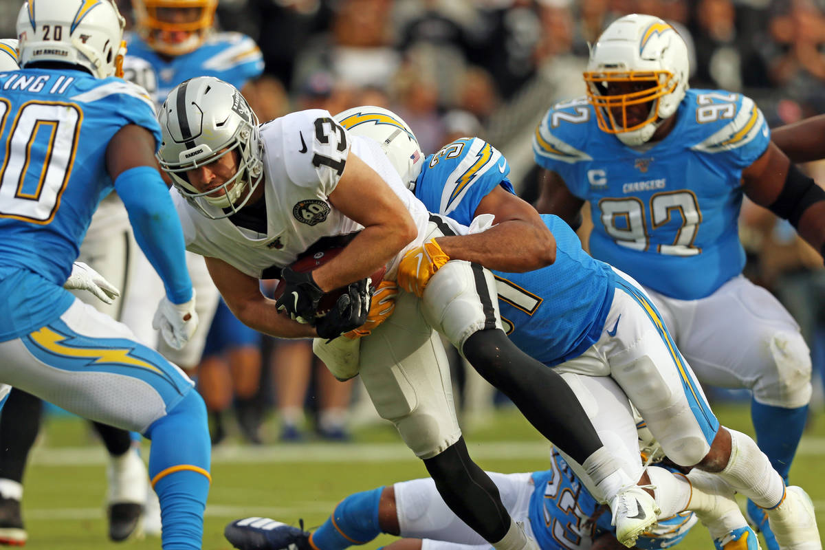 Oakland Raiders wide receiver Hunter Renfrow (13) is swarmed by Los Angeles Chargers defensive ...