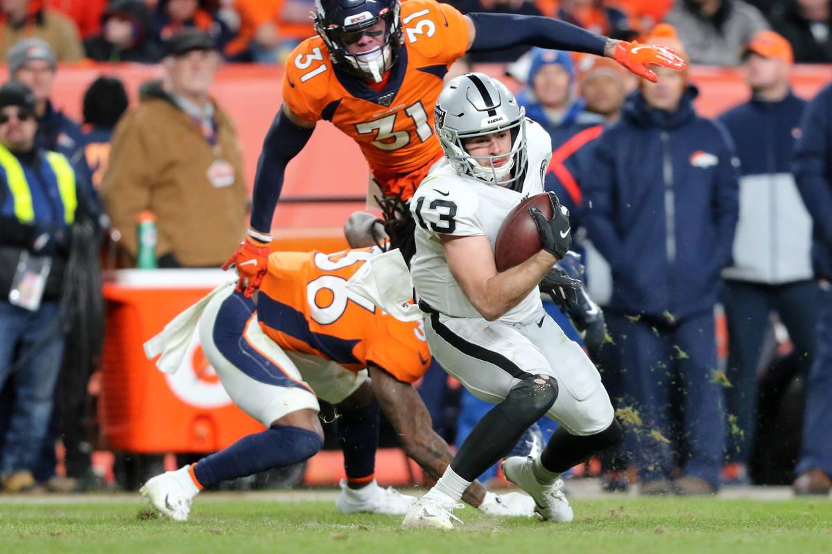Oakland Raiders wide receiver Hunter Renfrow (13) catches the football as Denver Broncos defens ...