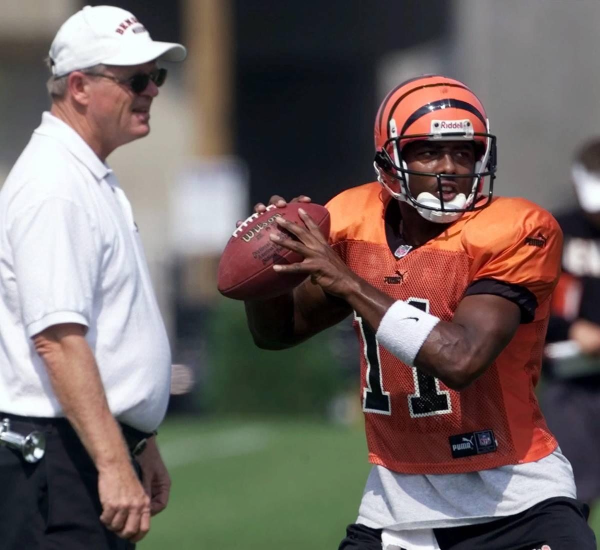 Cincinnati Bengals quarterback Akili Smith (11) sets to throw a pass as head coach Bruce Coslet ...