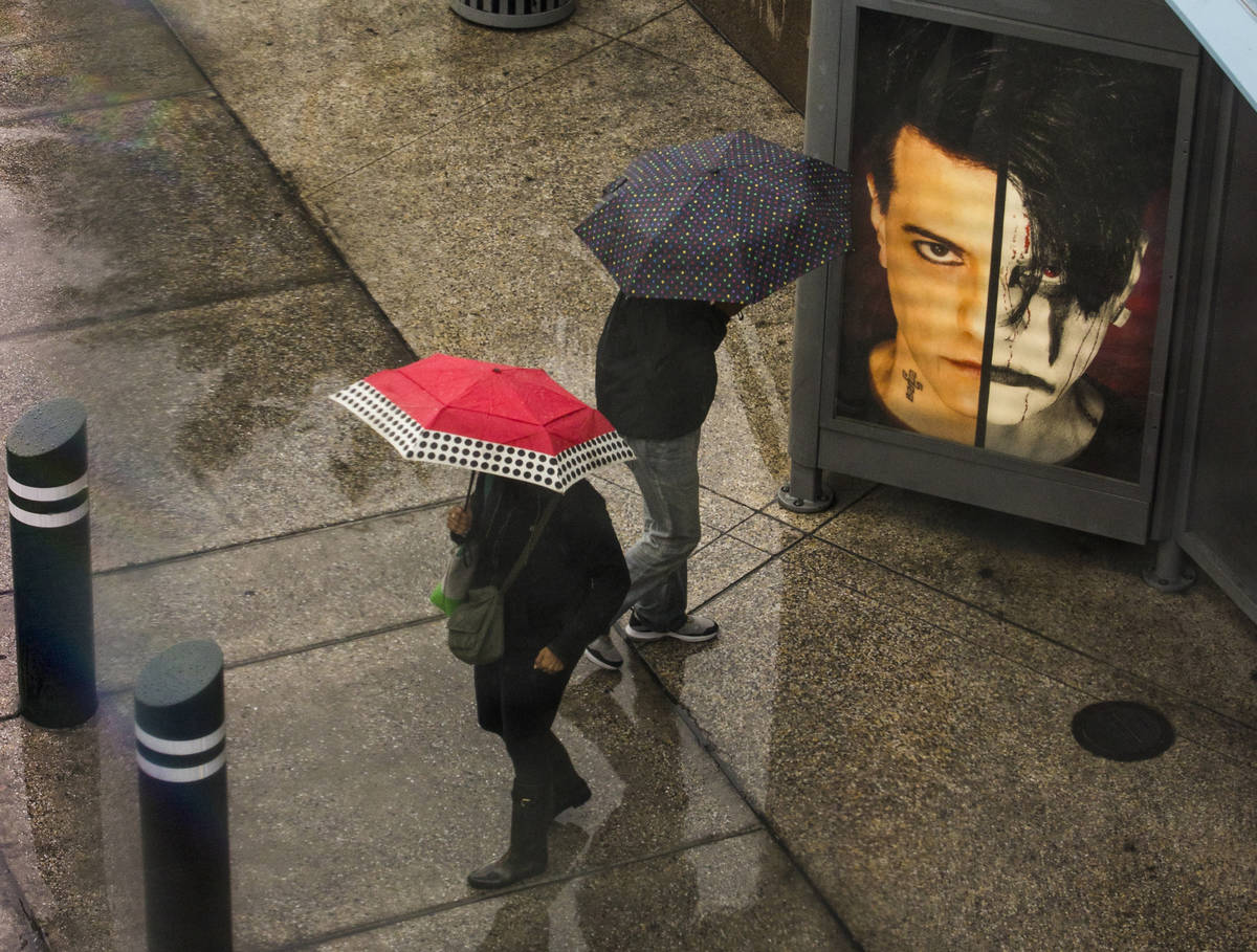 Pedestrians stand under umbrellas in the rain at a bus stop about the Fashion Show mall along t ...