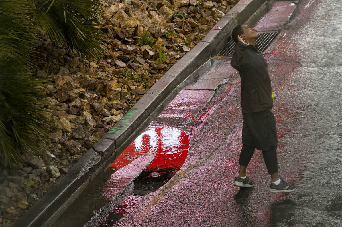 A pedestrian looks up to the rain as he walks past the Fashion Show mall along the Las Vegas St ...