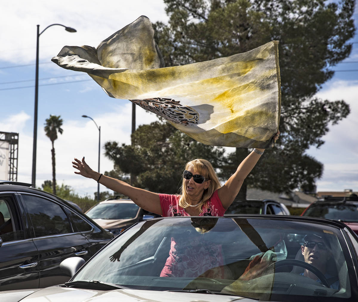 Pam Dunleavy waves a flag as she worships with her husband Dr. Sean Dunleavy at an Easter servi ...