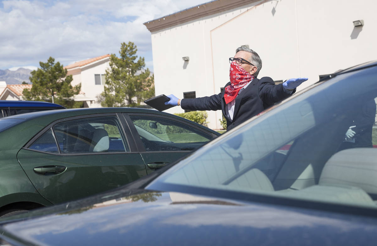 Pastor Paul Marc Goulet walks among cars as he leads an Easter service in the parking lot at In ...