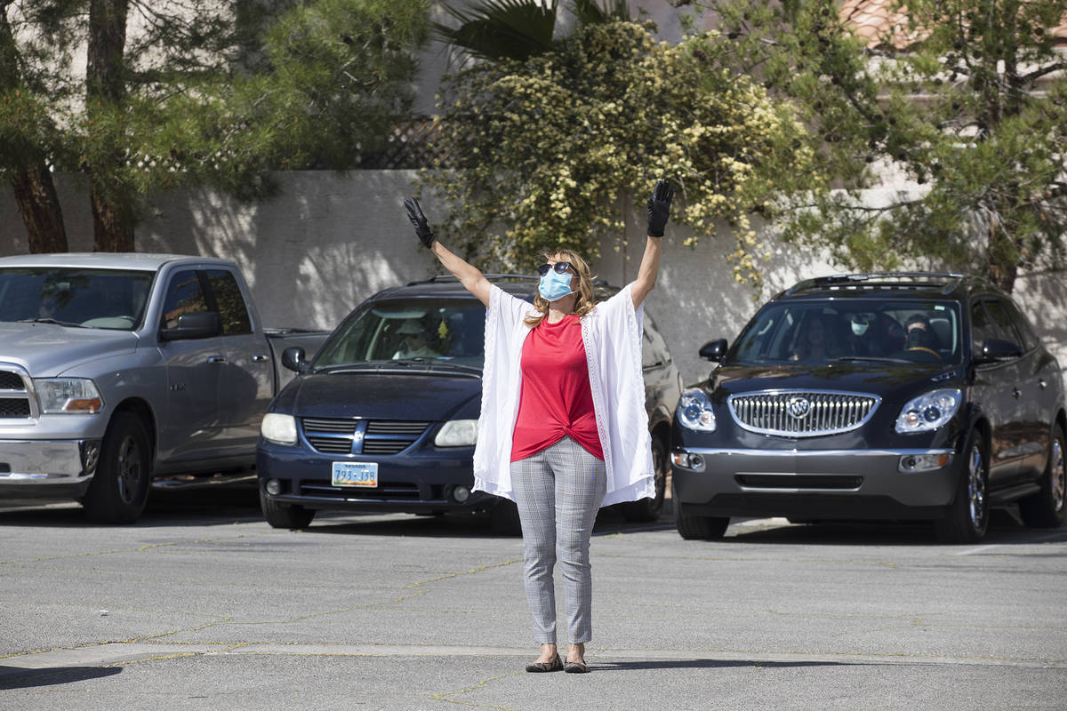 Usher Della Frank worships alongside guests in their cars at an Easter service in the parking l ...