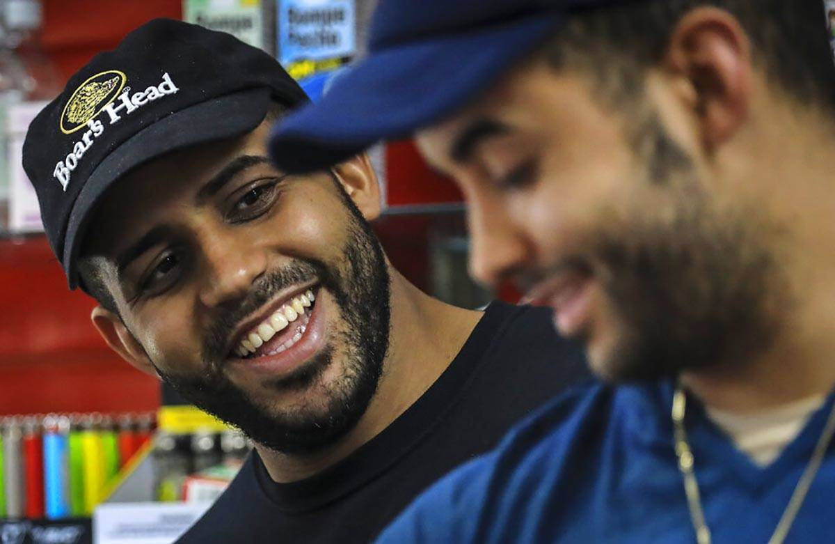 Alex Batista, left, talks with his brother Eudis Batista, owners of Deli-licious delicatessen i ...
