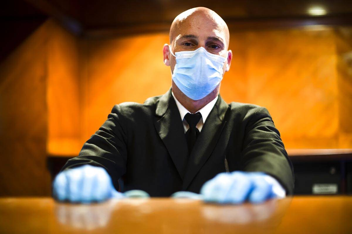 Concierge Joe DeLuca, poses for a photograph at the front desk of an apartment building in New ...