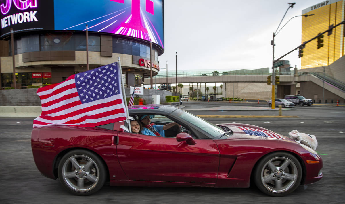 A participant flies an American flag as vehicles make their way up the Las Vegas Strip during t ...
