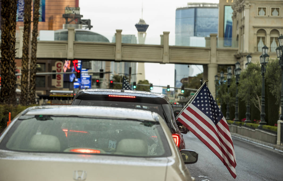 Some participants fly American flags as vehicles make their way up the Las Vegas Strip during t ...