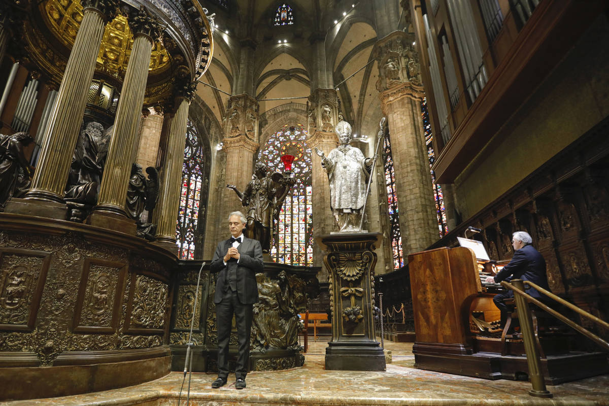 Italian singer Andrea Bocelli, left, performs inside an empty Duomo cathedral, on Easter Sunday ...