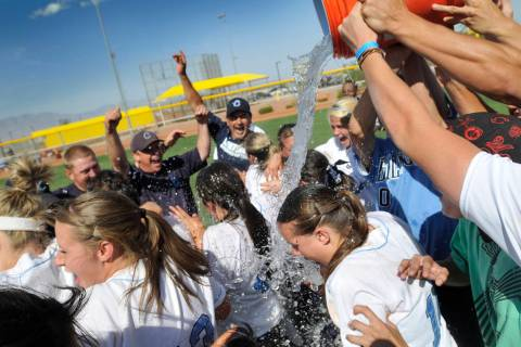Centennial High School softball team members get doused with ice water by fans as the celebrate ...