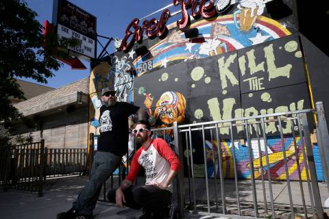 Dustin Hoots, left, and Jeff Lewis with their coronavirus mural on the boarded up windows of Ev ...
