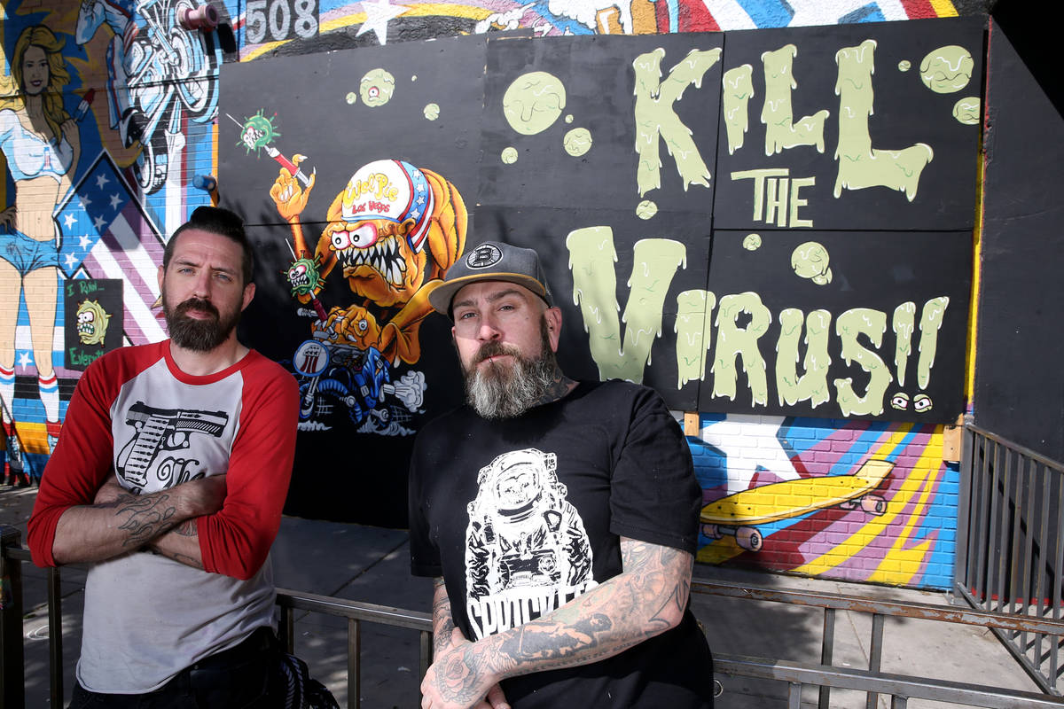 Jeff Davis, left, and Dustin Hoots with their coronavirus mural on the boarded up windows of Ev ...
