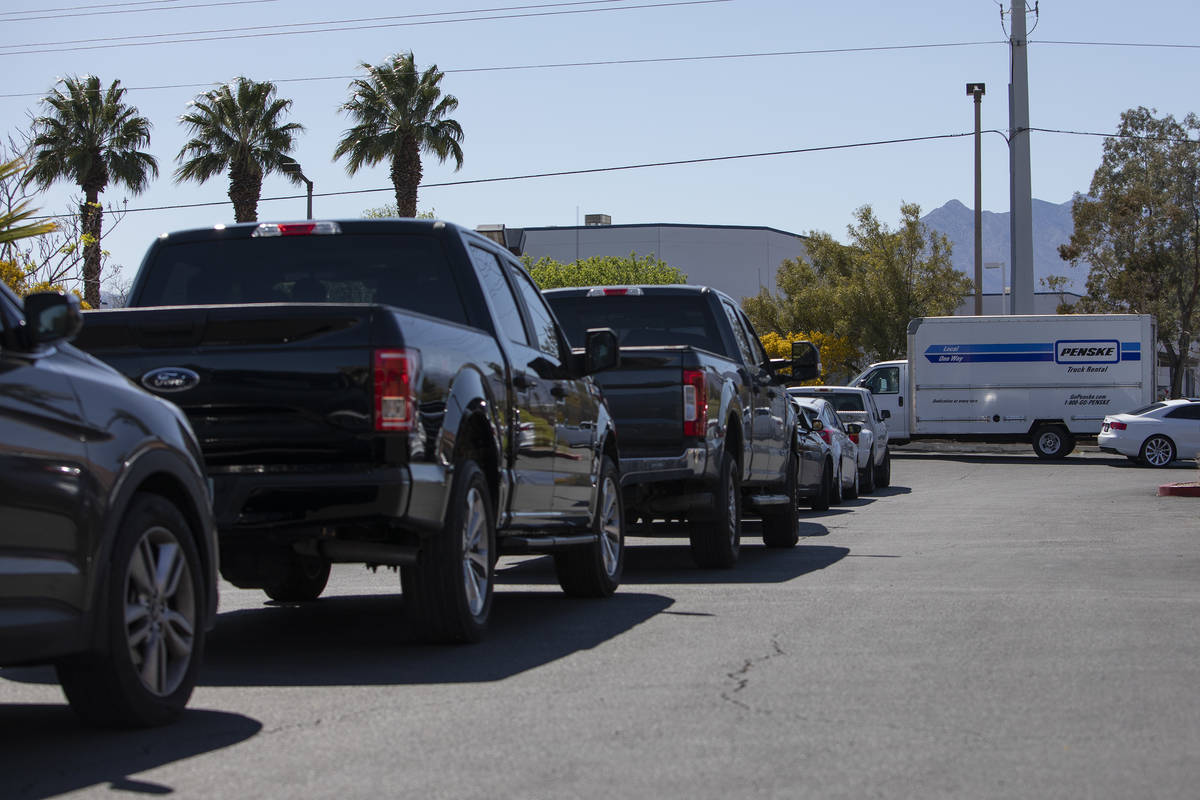 Cars line up for drive-through COVID-19 antibody testing, which took place out of the back of a ...