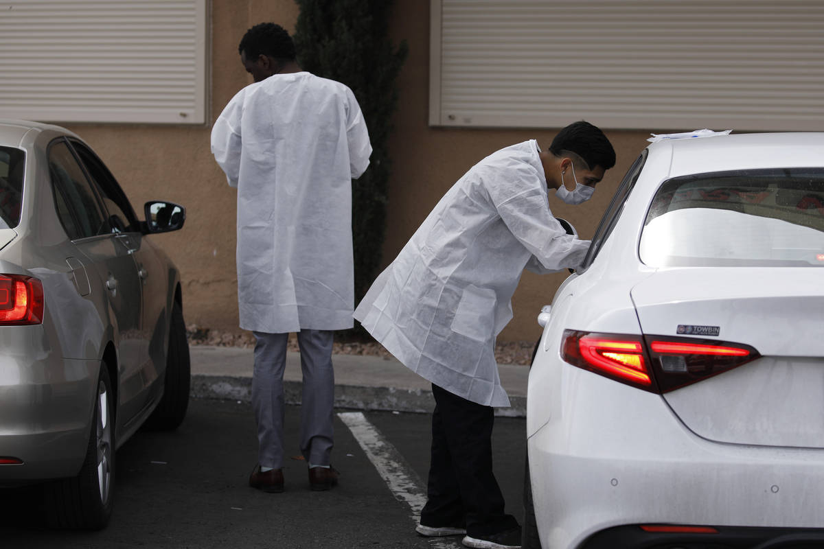 A caregiver, right, administers a coronavirus test to a person in a car at the Sahara West Urge ...
