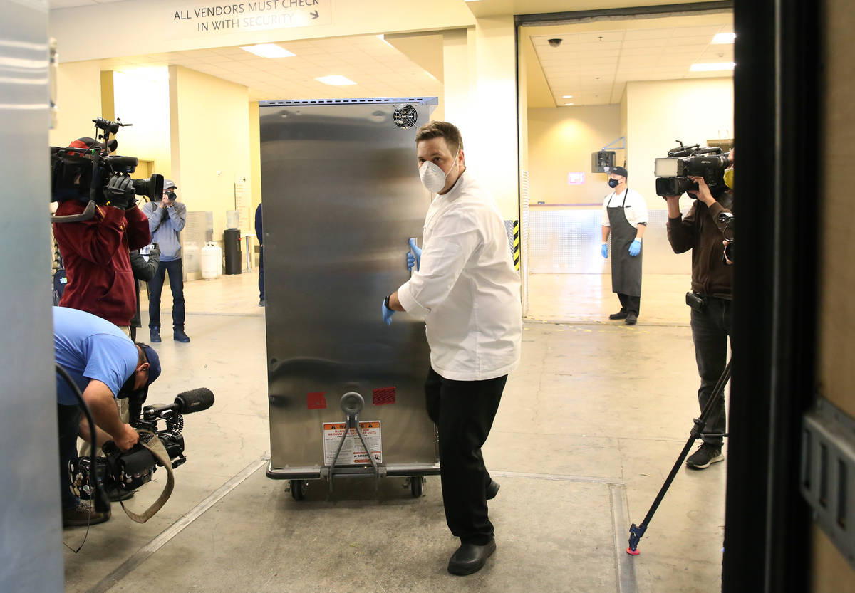 Thomas Griese, executive chef at Sage Restaurant, loads hot meals, prepared by chefs from the M ...