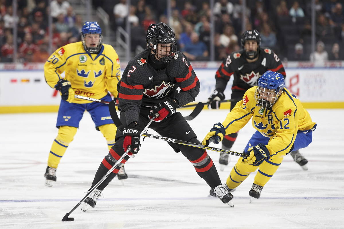 Canada's Justin Barron (2) is pursued by Sweden's Karl Henriksson (20) and Arvid Costmar (12) d ...