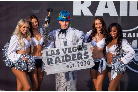 Painter Angel Ayala poses with a hammer between the Raiderettes during a special announcement a ...