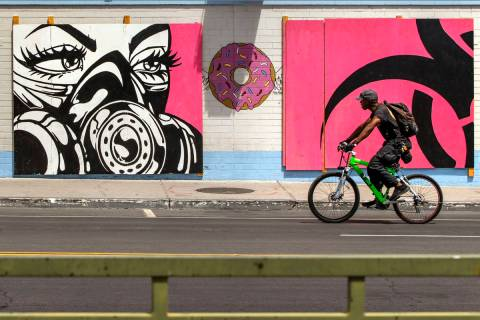 A cyclist rides past a mural by Franky Aguilar outside Donut Bar in Downtown Las Vegas on Su ...