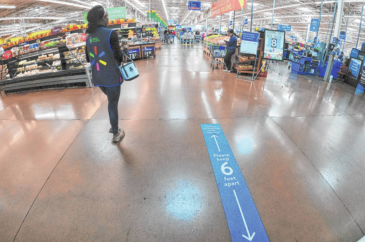 A sign at the entrance of Walmart Supercenter, 3950 W Lake Mead Boulevard, tells people to prac ...