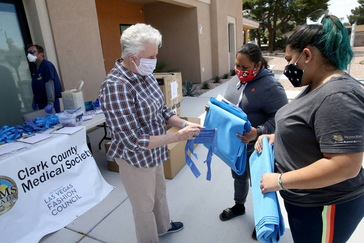 Denise Selleck, executive director of Clark County Medical Society, gives mask fabric to Rita O ...