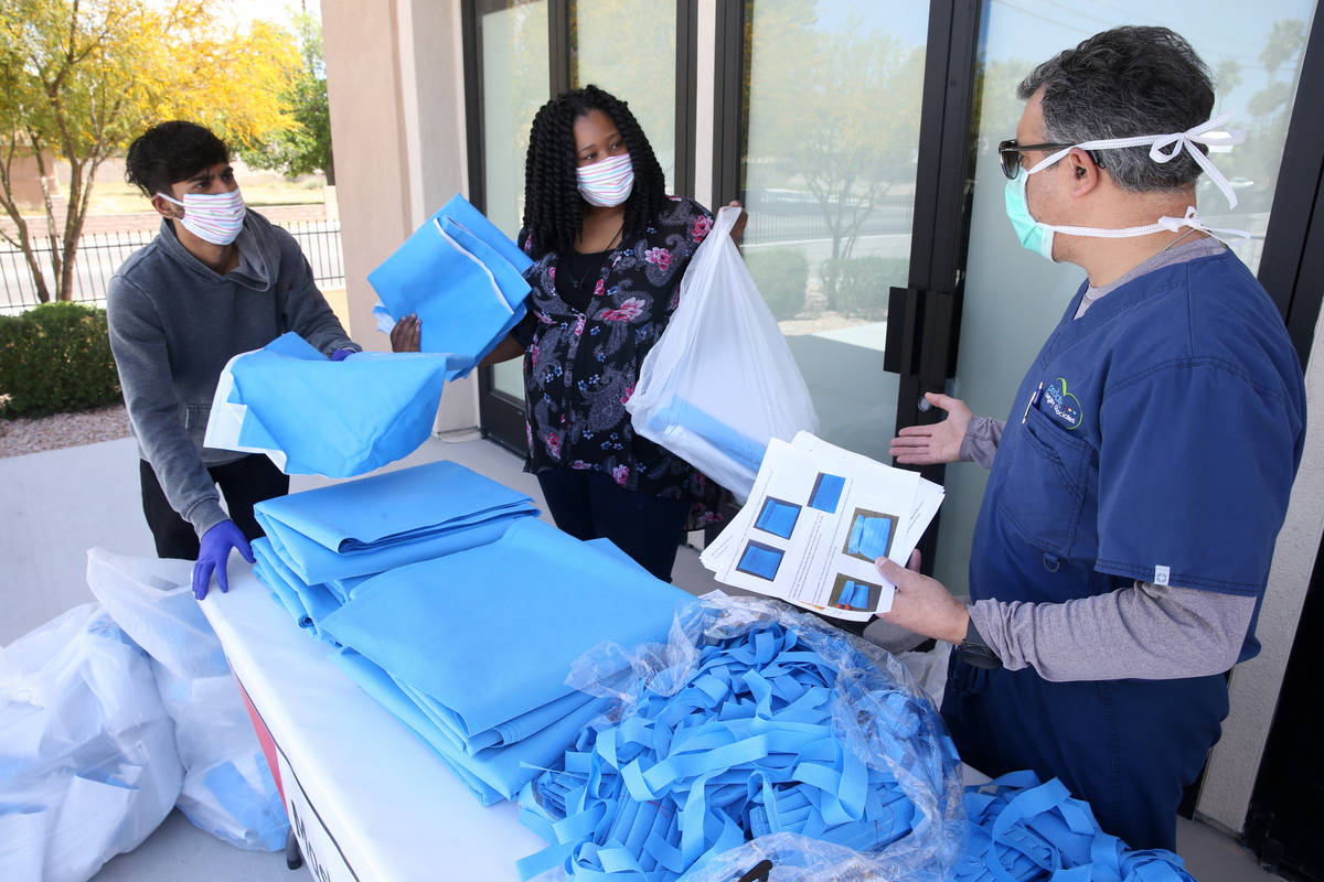 Dr. Nicholas Fiore, right, organizes mask fabric with Brittany Green, and Shalan Hassin, of Cla ...