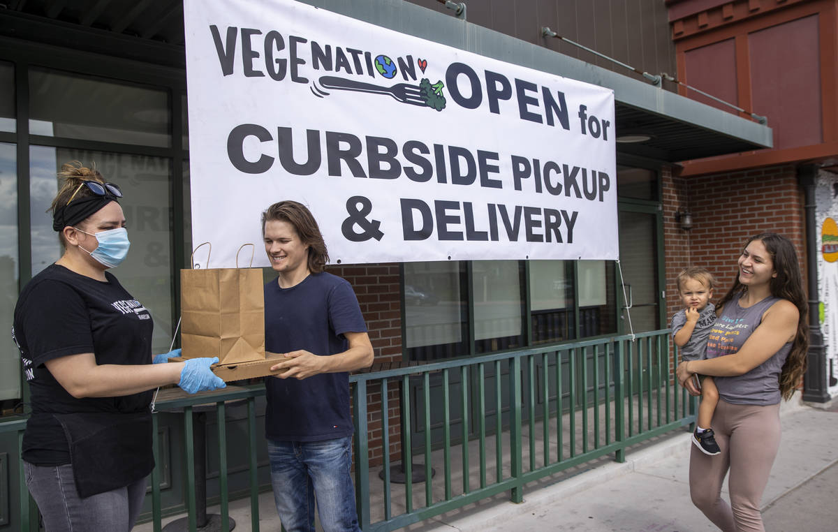 Vegenation's Rebecca Lemperle, left, hands over a food order to customer Matthew Badger with hi ...