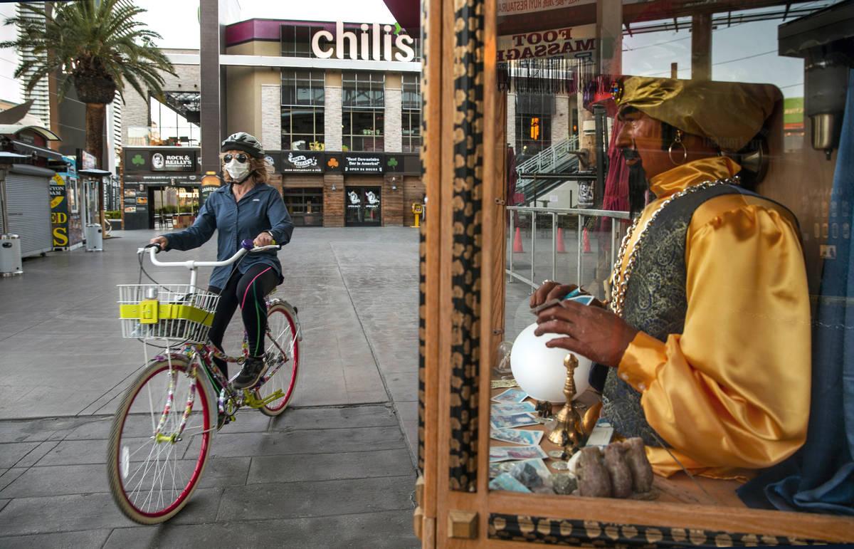 Jean Boccelli pedals past a Zoltar Fortune Teller machine near Chili's Grill & Bar along La ...
