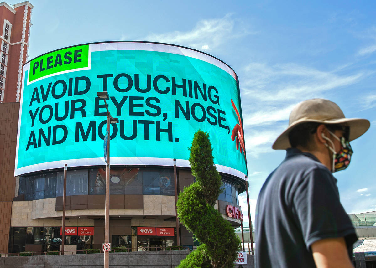 A pedestrian passes a large billboard addressing how to prevent the spread of the coronavirus ...