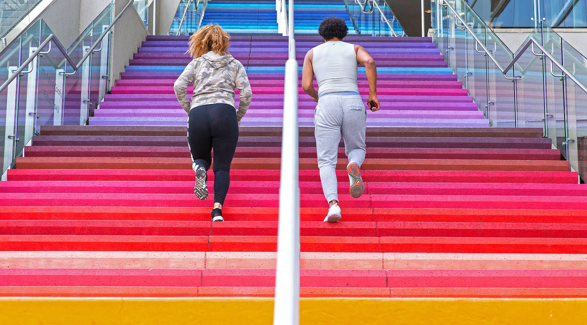 Jared Jenkins, right, and Kayla Muaina run the stairs outside Fashion Show mall on the Strip on ...