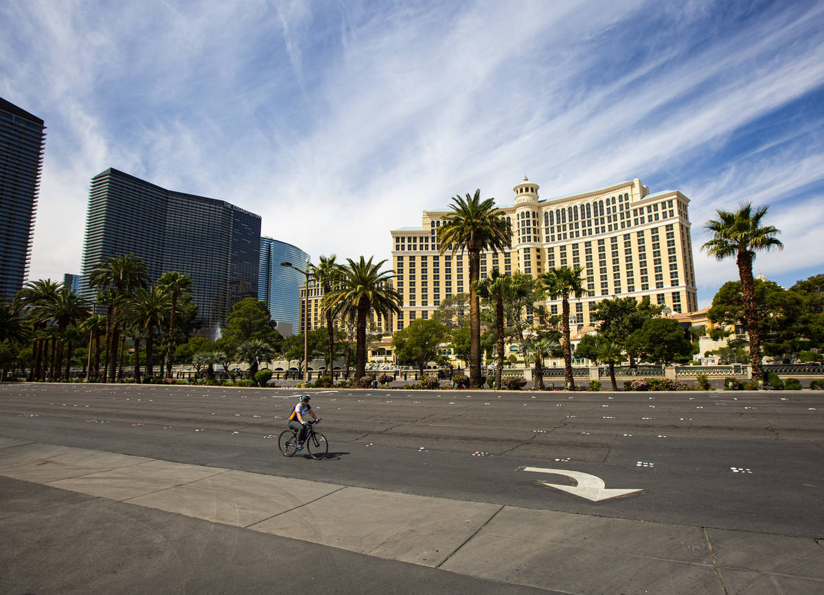 A cyclist makes their way past the Bellagio along the Las Vegas Strip on Thursday, April 16, 20 ...