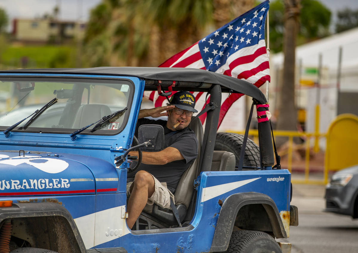 Greg Whalen salutes flag wavers as he follows others in for a protest at the Grant Sawyer State ...