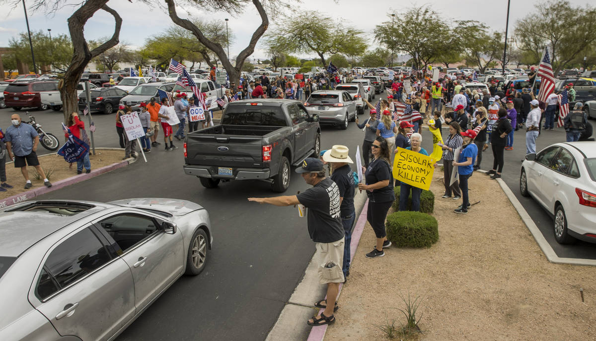 Protesters continue to welcome others arriving to the Reopen Nevada protest at the Grant Sawyer ...