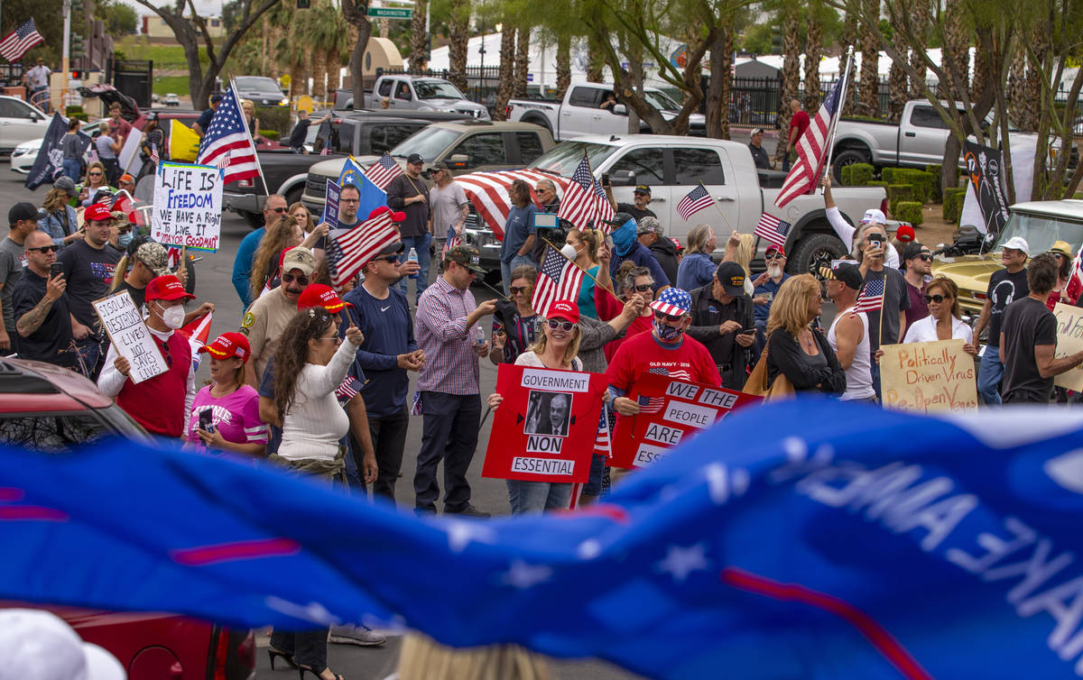 Protesters chant and welcome others arriving to the Reopen Nevada protest at the Grant Sawyer S ...