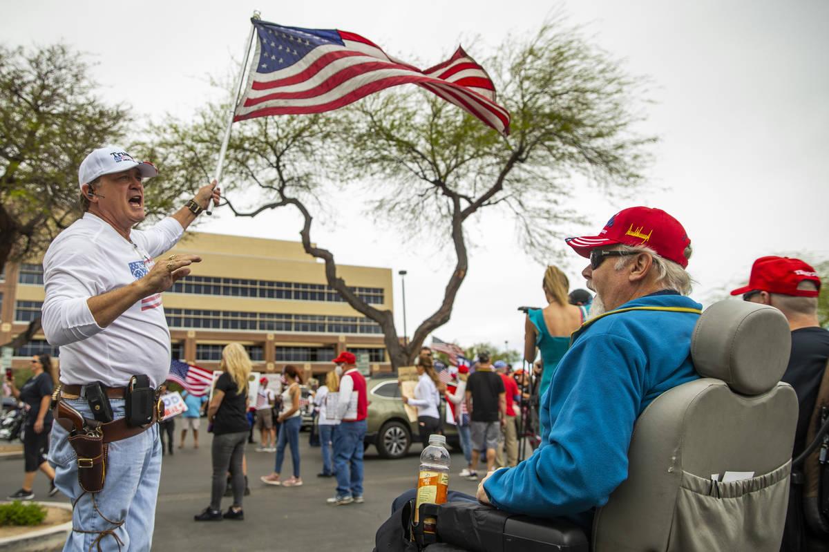 Protesters Scott Bockert, left, and Craig Schmidt talk politics during the Reopen Nevada protes ...