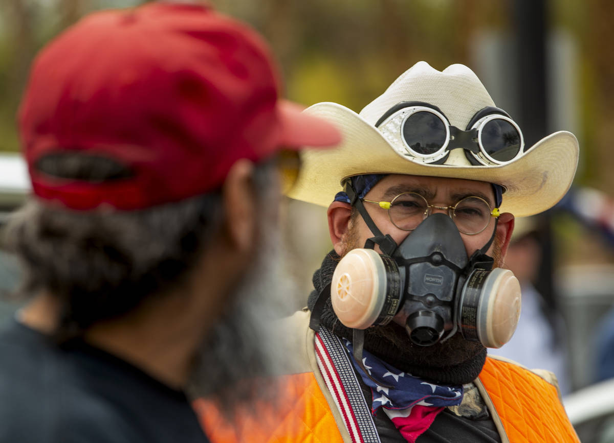 Giles Smith, right, wears a mask while joining many others during the Reopen Nevada protest at ...
