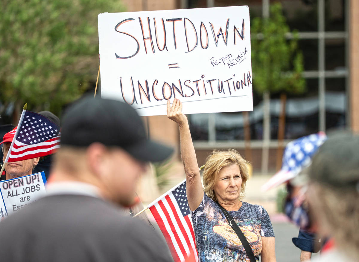 Sue Thiel, middle, takes part in a protest outside the Grant Sawyer State Office Building organ ...