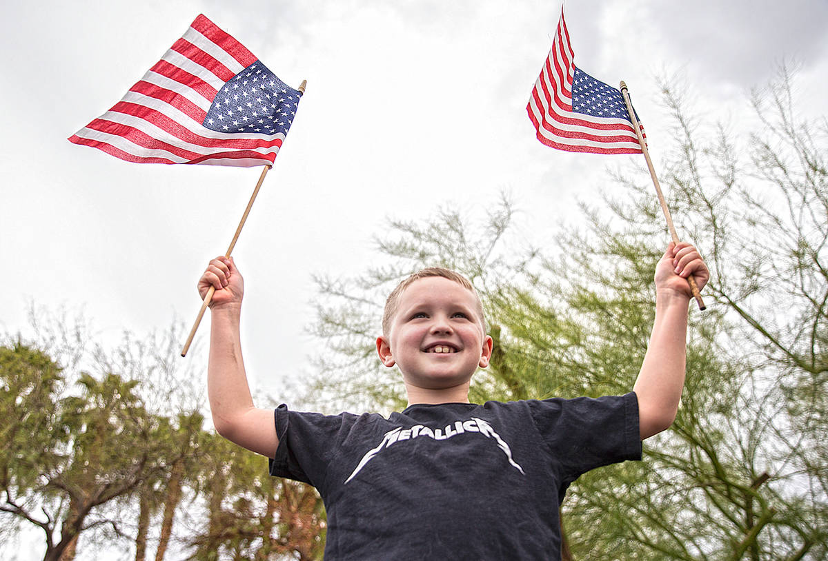Jackson Hrustyk, 8, waves American flags during an event organized by Reopen Nevada at the Gran ...