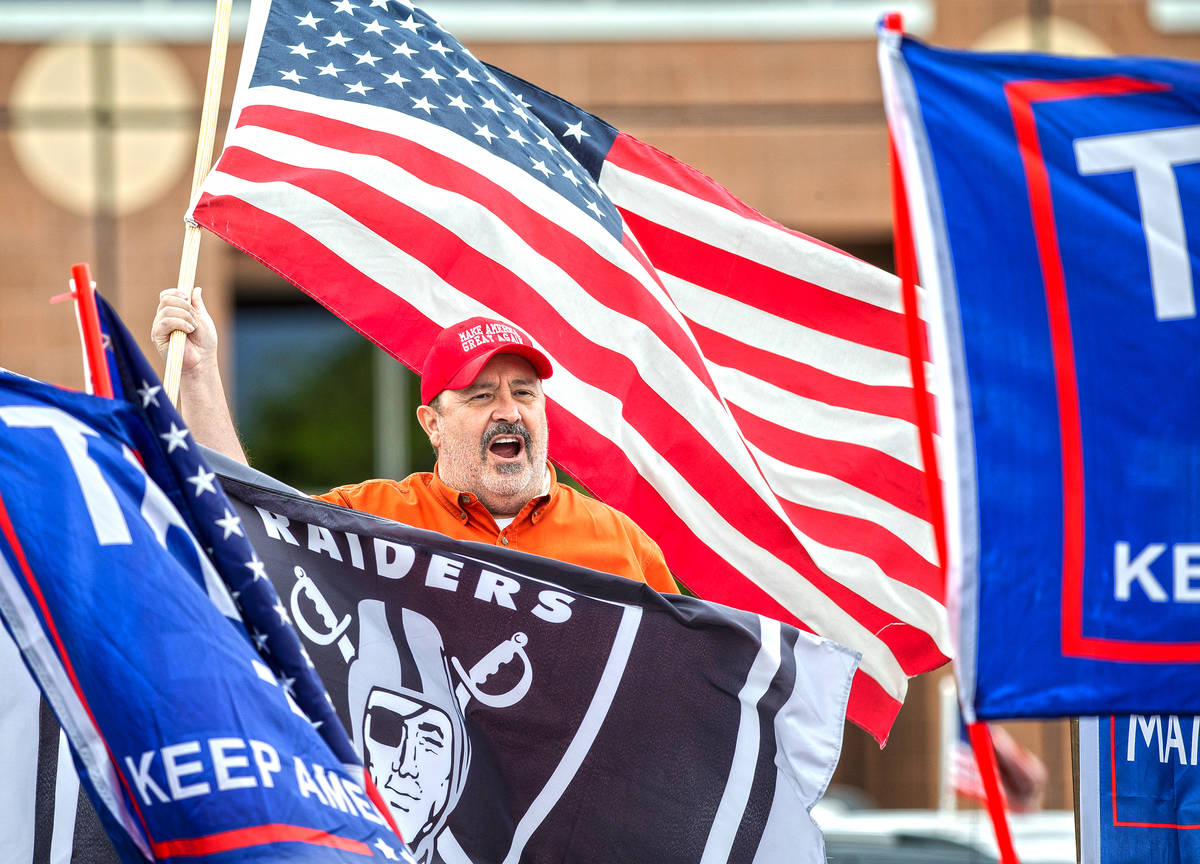 Dave Moreno waves an American flag during an event organized by Reopen Nevada at the Grant Sawy ...