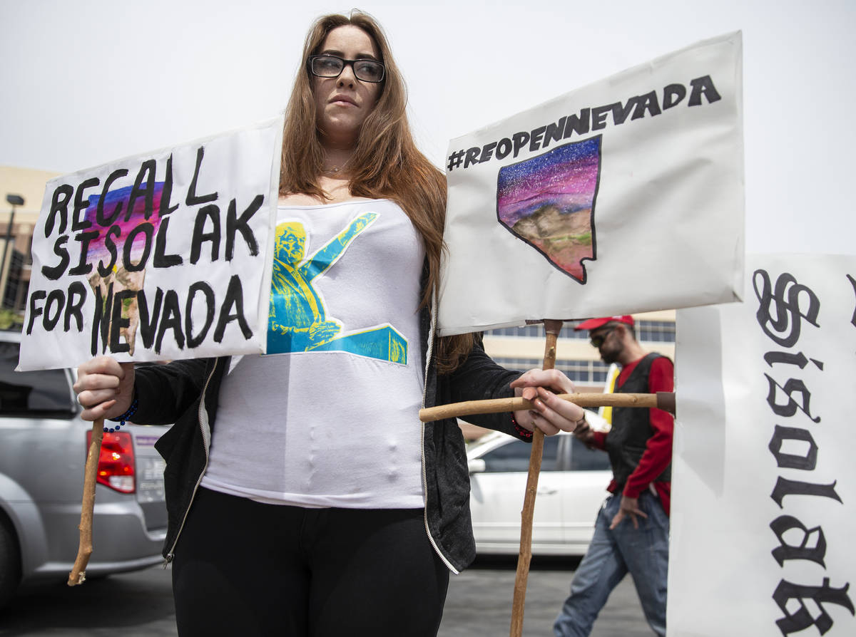 Natalie Thomas, the Facebook organizer of the Reopen Nevada event, holds signs opposing Gov. St ...