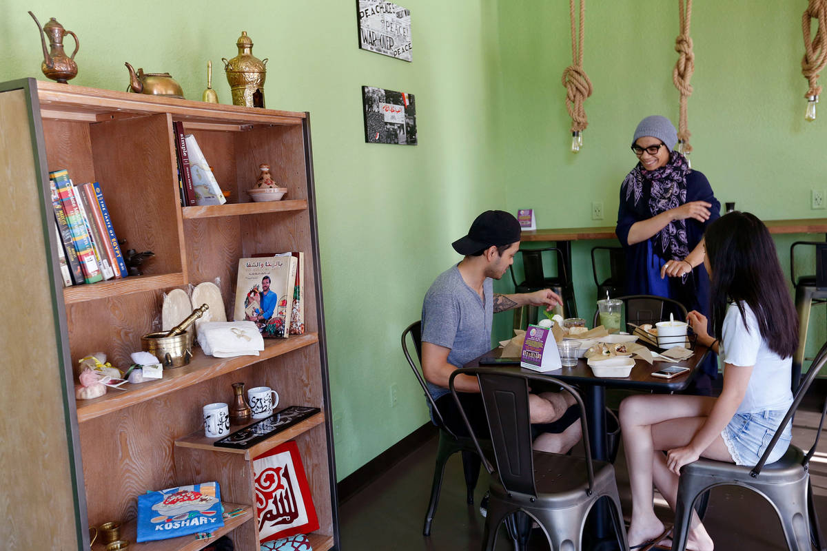 Pots owner/chef Iman Haggag, center, speaks to her customers Gray Murillo of Las Vegas and his ...