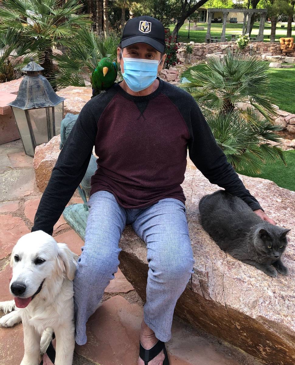 Las Vegas legend Wayne Newton is shown wearing a medical mask with his dog Bailey, Eclectus par ...