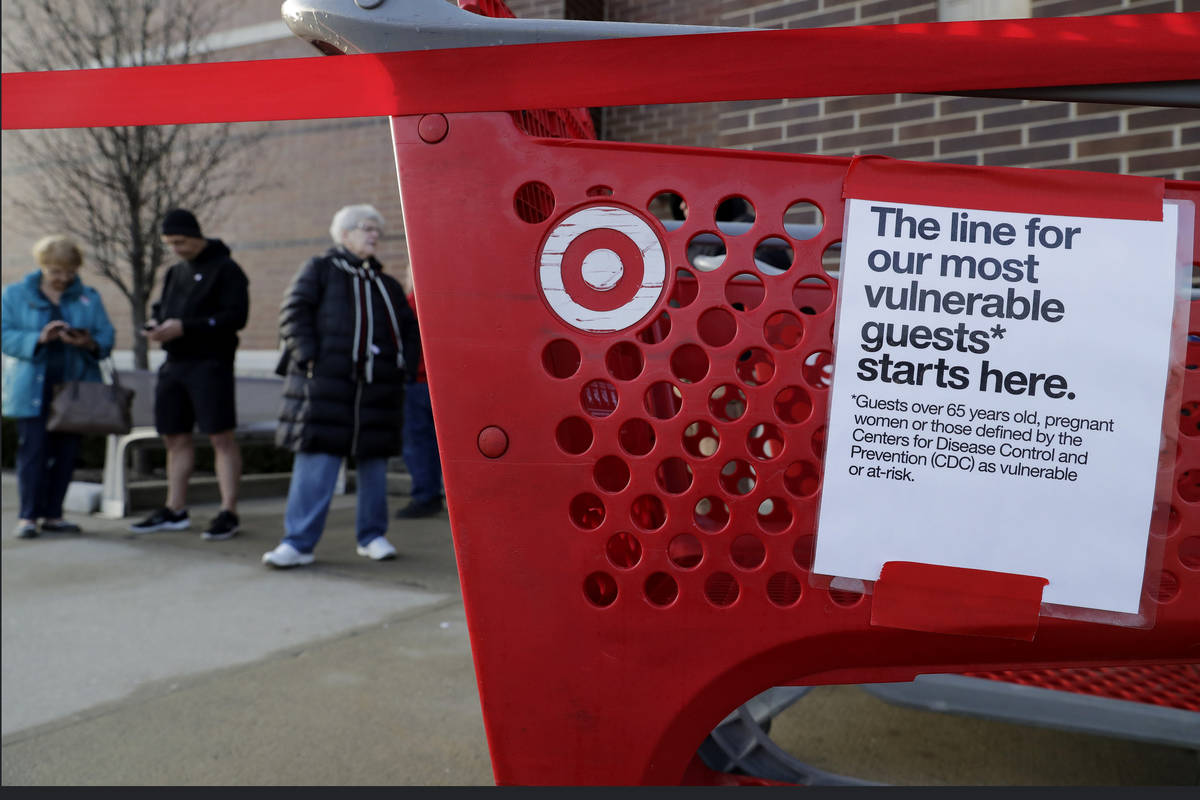 Shoppers wait to enter at a Target store in Glenview, Ill., Wednesday, March 25, 2020. Grocery ...