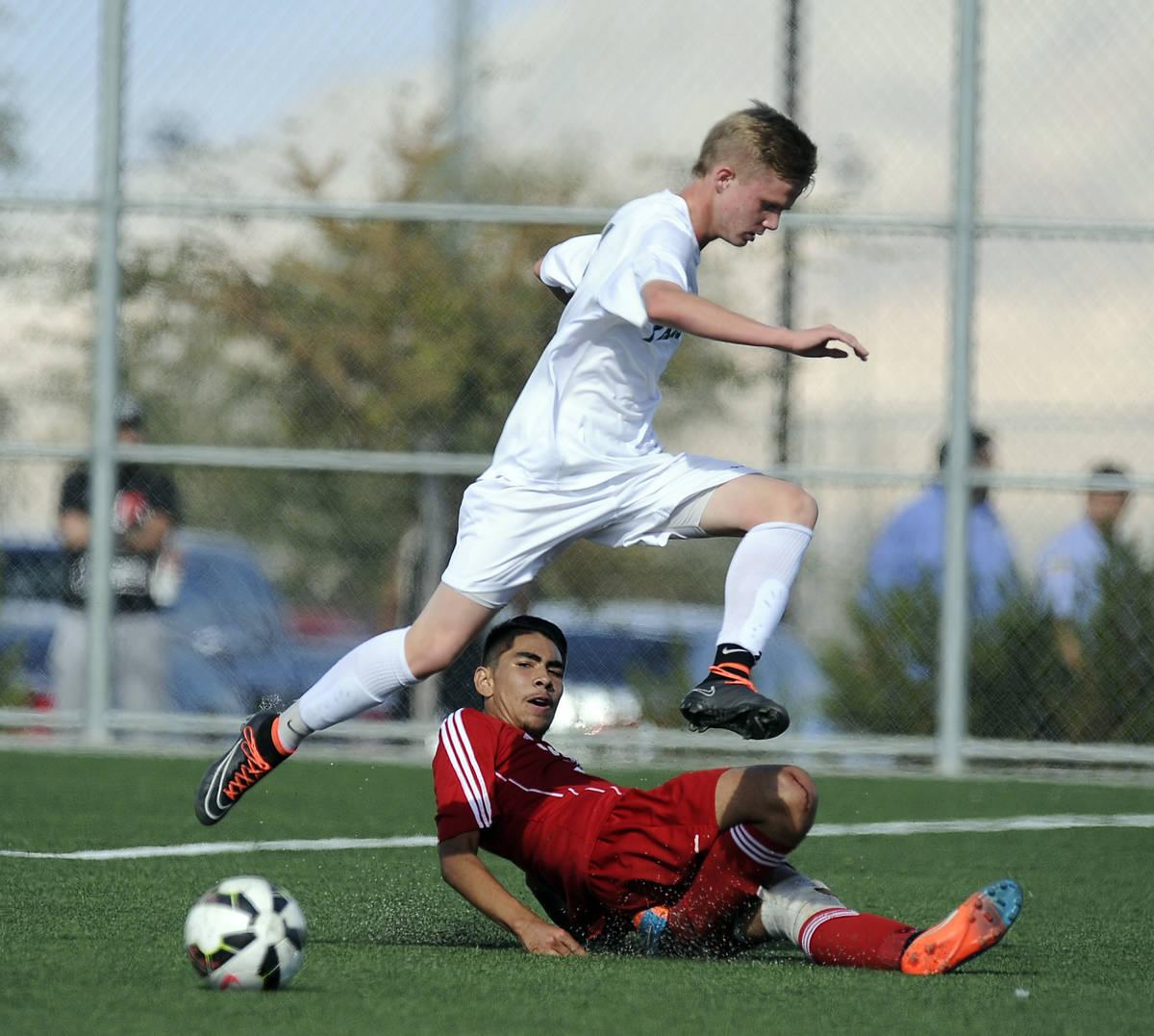 Palo Verde striker Presten Manthey jumps over the slide tackle of Valley defender Steve Favela ...